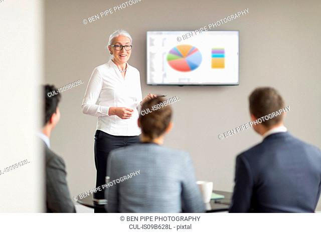 Over shoulder view of mature businesswoman giving office presentation
