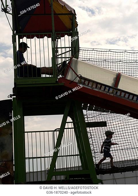 Man watchting children play at the Sussex County Fair in Augusta, New Jersey