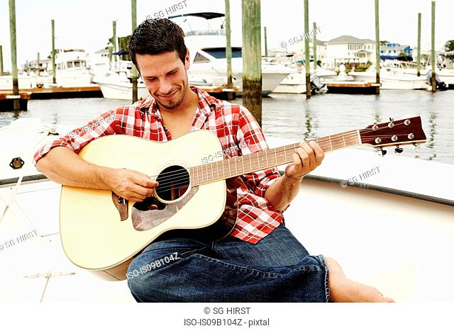 Young man playing acoustic guitar on marina motorboat