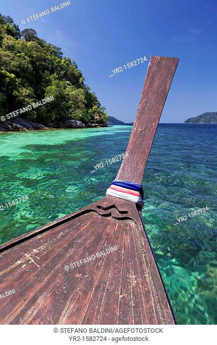 Bow of a longtail boat in front of the coastline of one of the many small islands within the Tarutao National Marine Park, Thailand