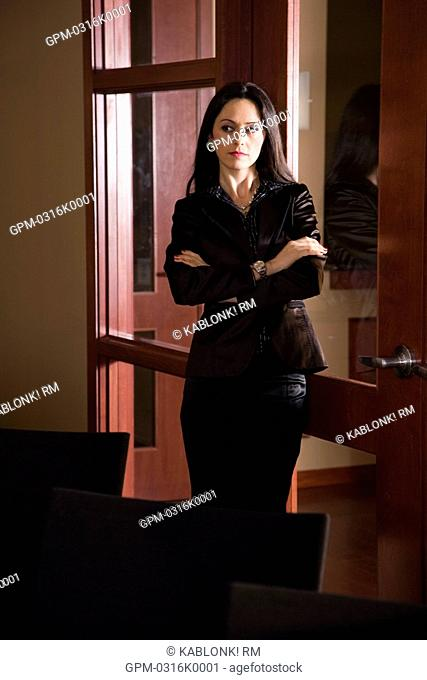 Portrait of mid adult businesswoman standing in boardroom with arms crossed