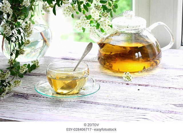 Tea in a transparent cup and a bouquet from branches of a blossoming elder