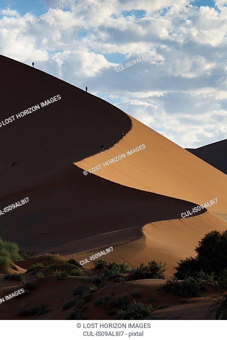 Two people climbing giant sand dune, Sossusvlei National Park, Namibia