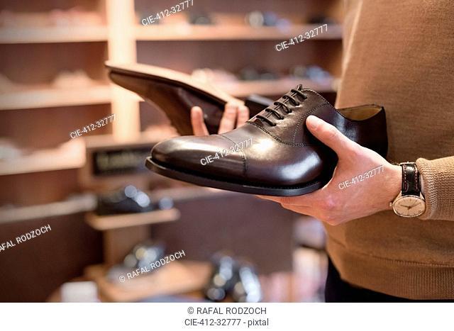 Businessman browsing dress shoes in menswear shop