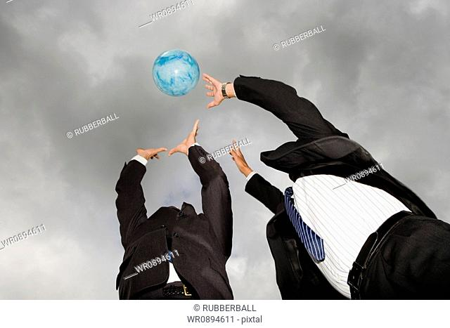 Low angle view of two businessmen playing with a ball