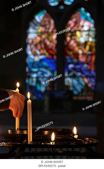 A man's hand lights a candle in a church with colourful stained glass window in the background; Northumberland, England