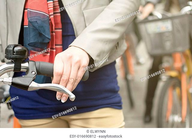 Closeup images of an Asian woman riding bicycle, focus on hand