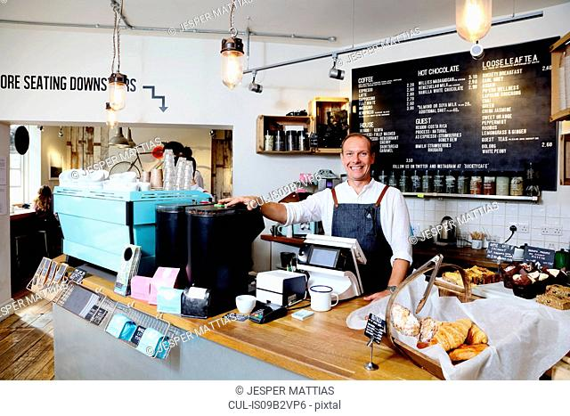 Portrait of male business owner behind counter of independent coffee shop