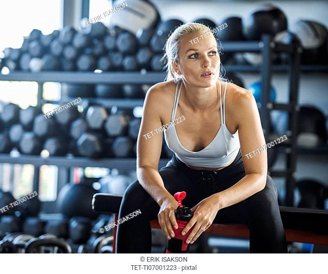 Young woman holding bottle in gym
