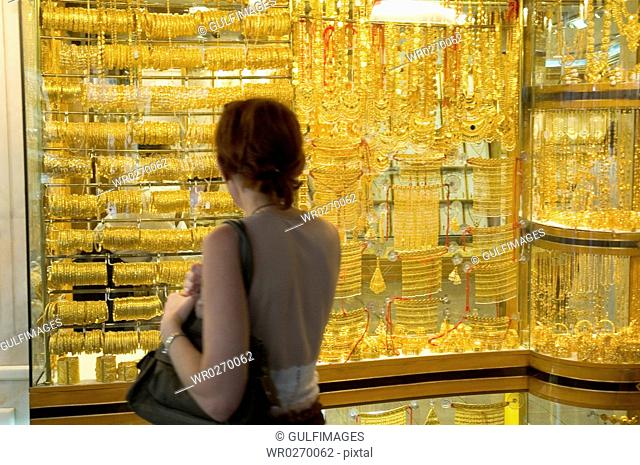 A woman looking at the jewelry seen on the store