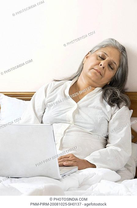 Woman napping while using a laptop