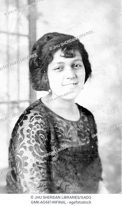 Half length portrait of a young African American woman, she is wearing a dark lace shirt and she is smiling, 1915