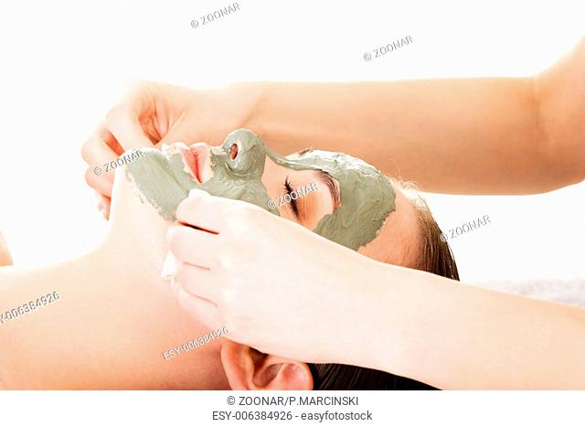 Beauty treatment in spa salon. Woman with facial clay mask