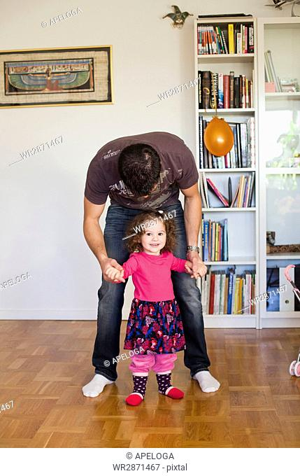 Cute girl walking with father on hardwood floor at home