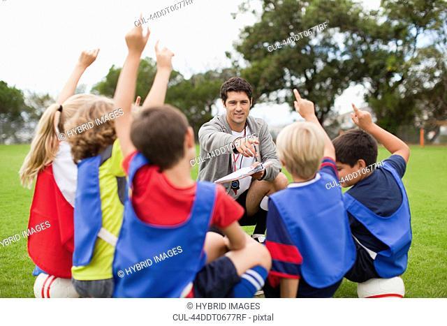 Children raising hands during practice