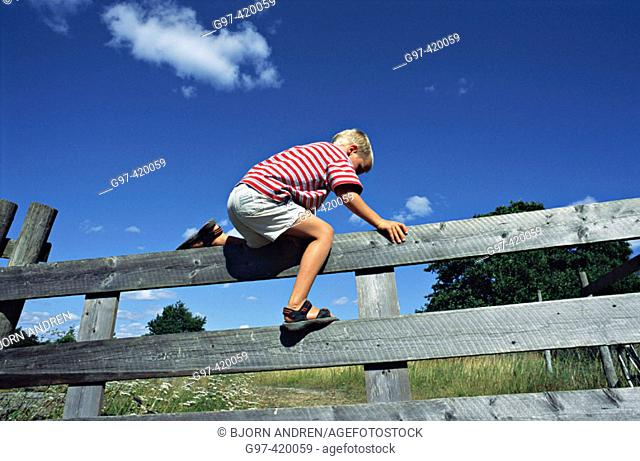 Boy climbing over a fence