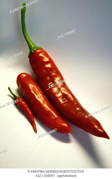 Three different types of red Peppers lined up by size