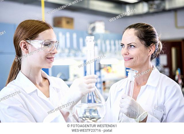 Two smiling scientists working together in lab