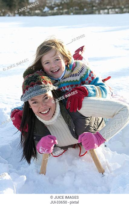 Portrait of smiling mother and daughter laying on sled in snow