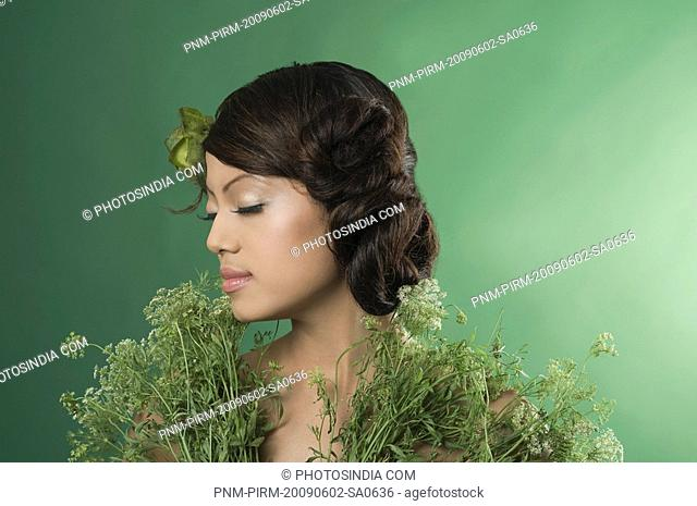 Beautiful woman posing with plants