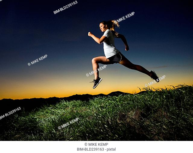 Caucasian woman running at sunset