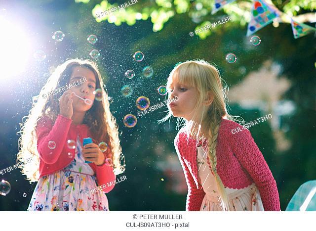 Two girls blowing bubbles in sunlit garden