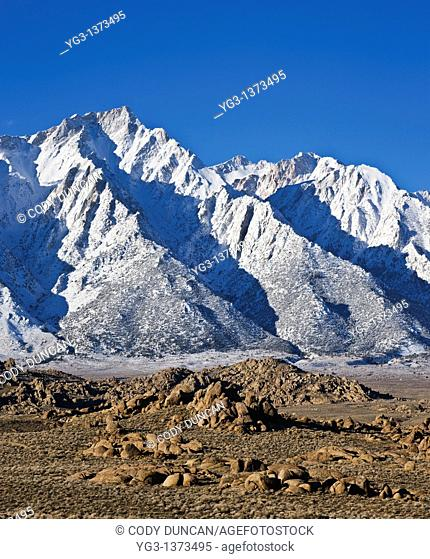 Granite rock formations of Alabama Hills with Lone Pine peak and Sierra Nevada mountains in background, California