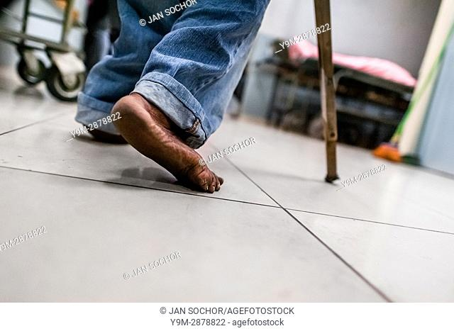 A Salvadoran barefoot man limps in the hospital corridor while seeking a medical help in the emergency department of a public hospital in San Salvador