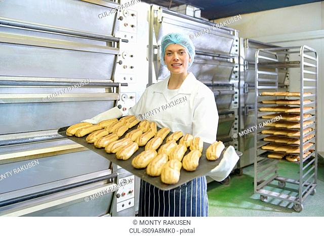 Baker holding tray of baked pastries