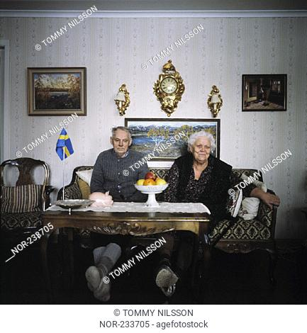 An old couple sitting in their living room and looking at camera