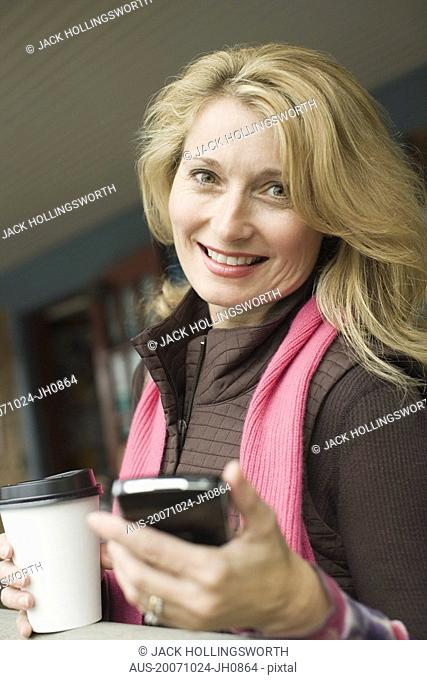 Portrait of a mature woman holding a mobile phone and smiling