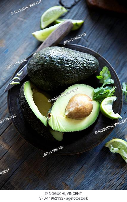 Avocados, whole and halved with a knife on a plate
