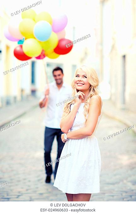 summer holidays, celebration and relationships concept - woman and man with colorful balloons in the city
