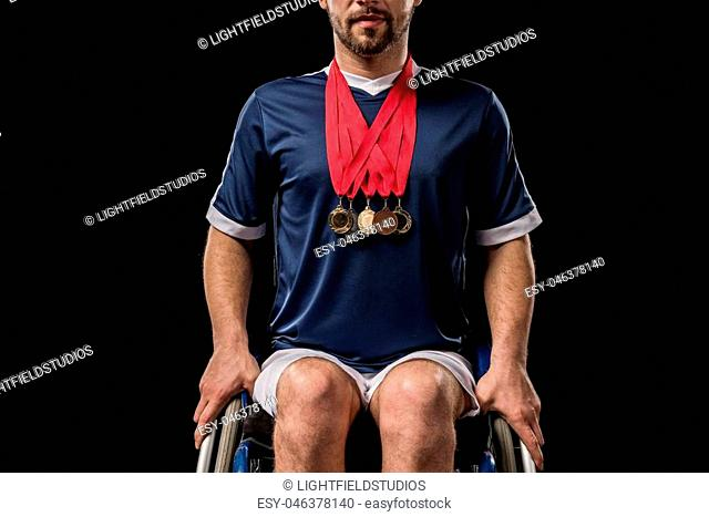 cropped view of paralympic in wheelchair with gold medals on his neck isolated on black