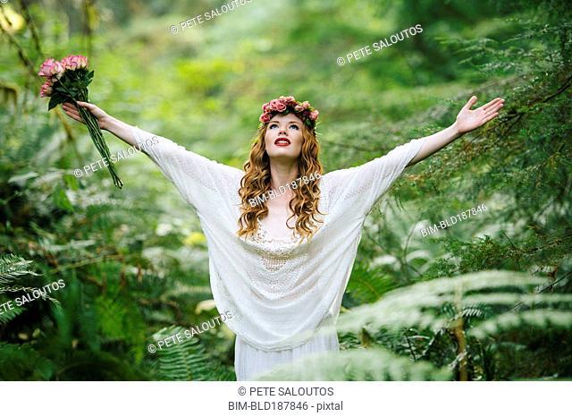 Caucasian woman wearing flower crown in forest