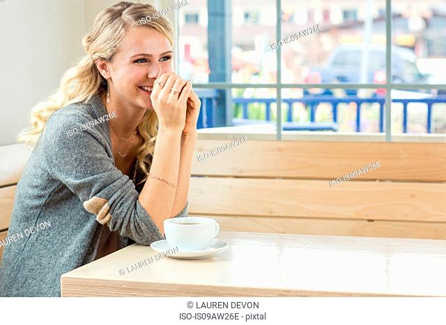 Young woman sitting at table with tea and saucer, resting on elbows, looking away smiling