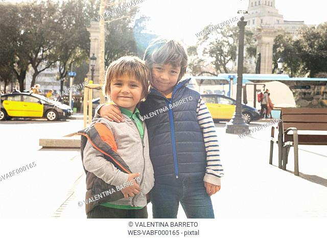 Spain, Barcelona, portrait of two little brothers standing arm in arm at backlight