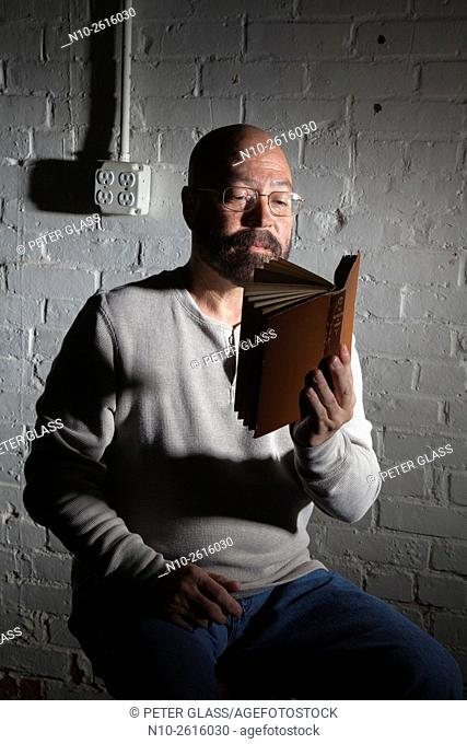 Middle age bald man with a beard and glasses, reading a book