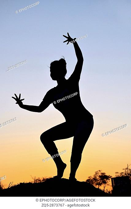 Silhouette of young girl in classical dance pose near mountain, Pune, Maharashtra
