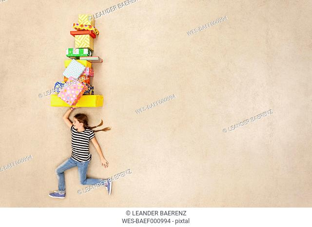 Girl balancing stack of presents