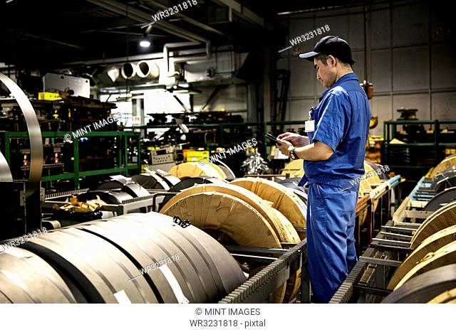 Japanese man wearing baseball cap and blue overall standing in factory, working