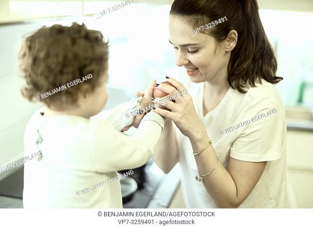 mother and child with apple in kitchen at home, in Munich, Germany