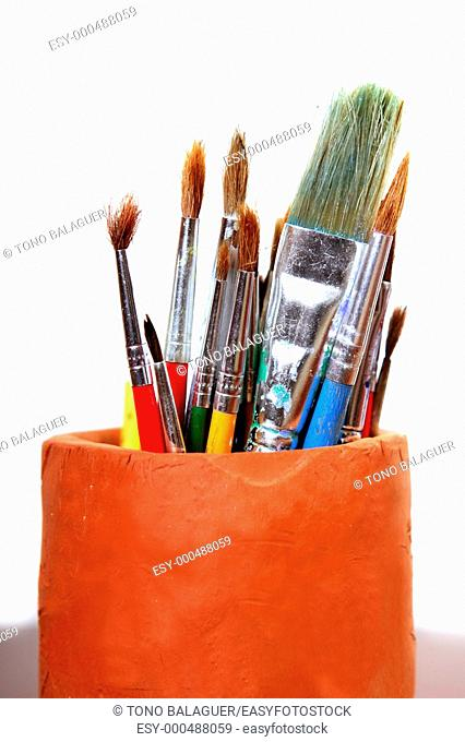 Artist used brushes clay pot isolated on white