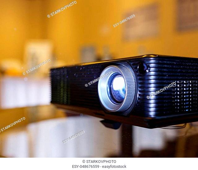 Modern technology, a black projector on the glass table prepared to broadcast video and presentations on a large screen in the audience