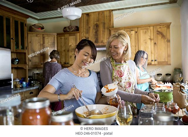 Smiling women canning tomato sauce in kitchen