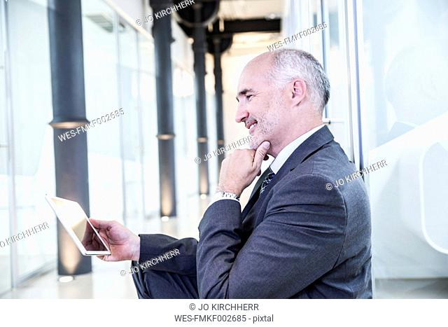 Mature businessman using digital tablet