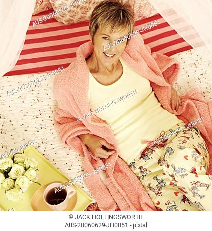 Portrait of a mature woman reclining on the bed and smiling