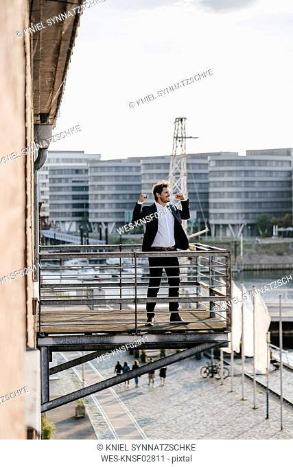 Businessman standing on balcony, flexing muscles