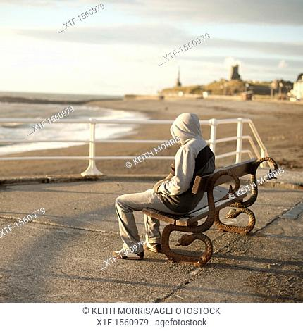 A young man wearing a hoodie sitting alone on a seaside bench, Aberystwyth Wales UK