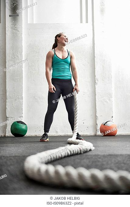 Woman holding battle rope in cross training gym